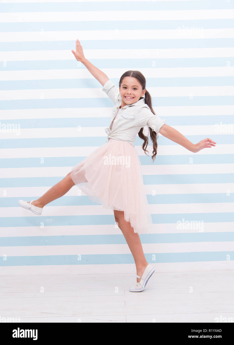 Child concept. Happy little child dancing. Child girl smile in fashion dress. Child and childhood. sense of freedom. - Stock Image