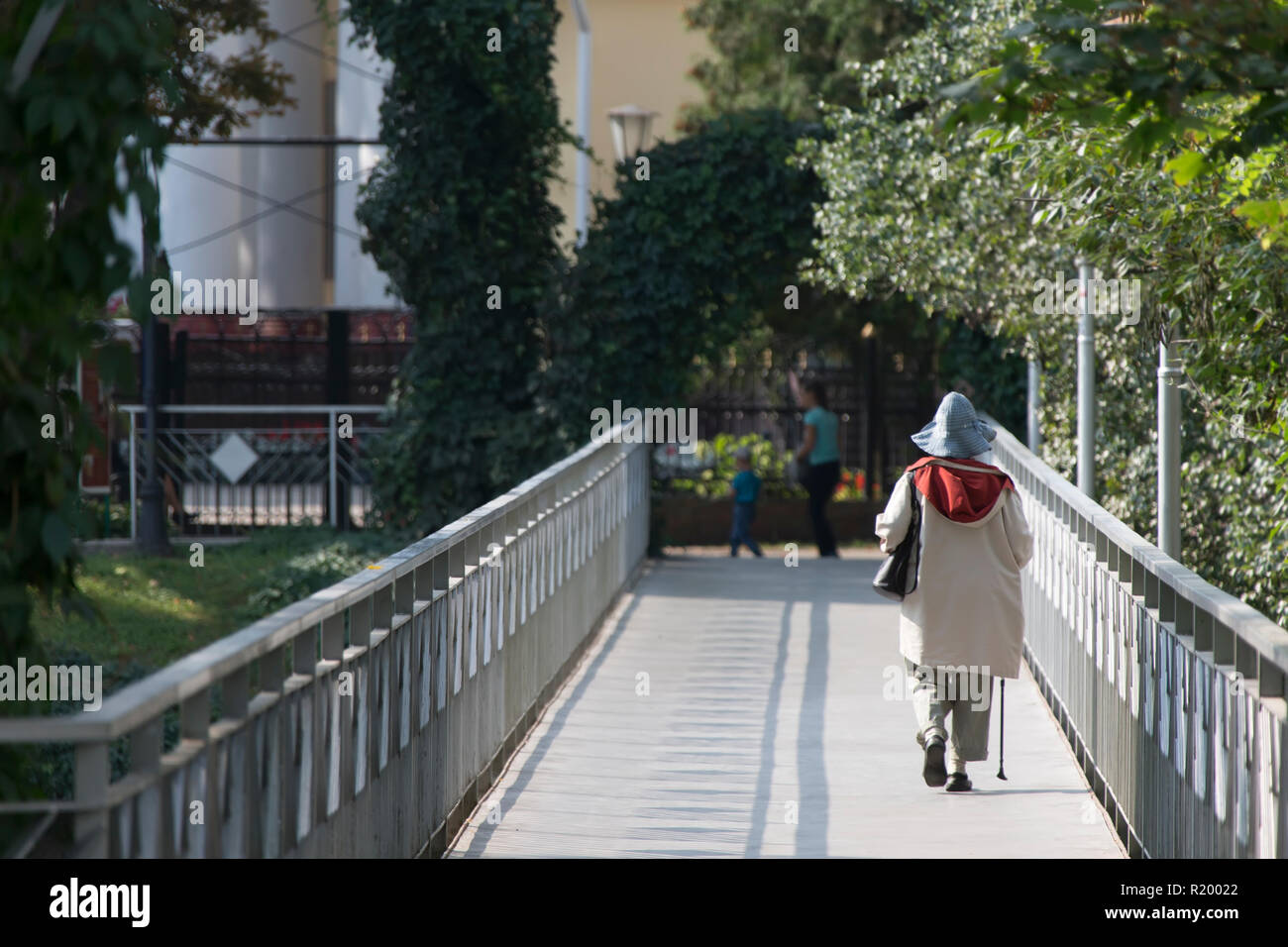 Old woman with a stick goes over the bridge - Stock Image