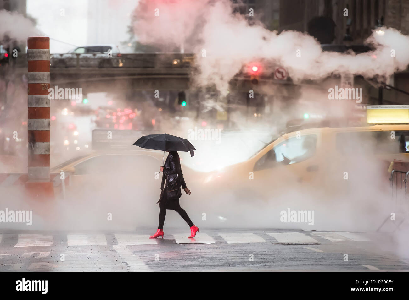 A woman with an umbrella and red high heels shoes is crossing the 42nd street in Manhattan. Taxi and steam coming out from from the manholes. - Stock Image