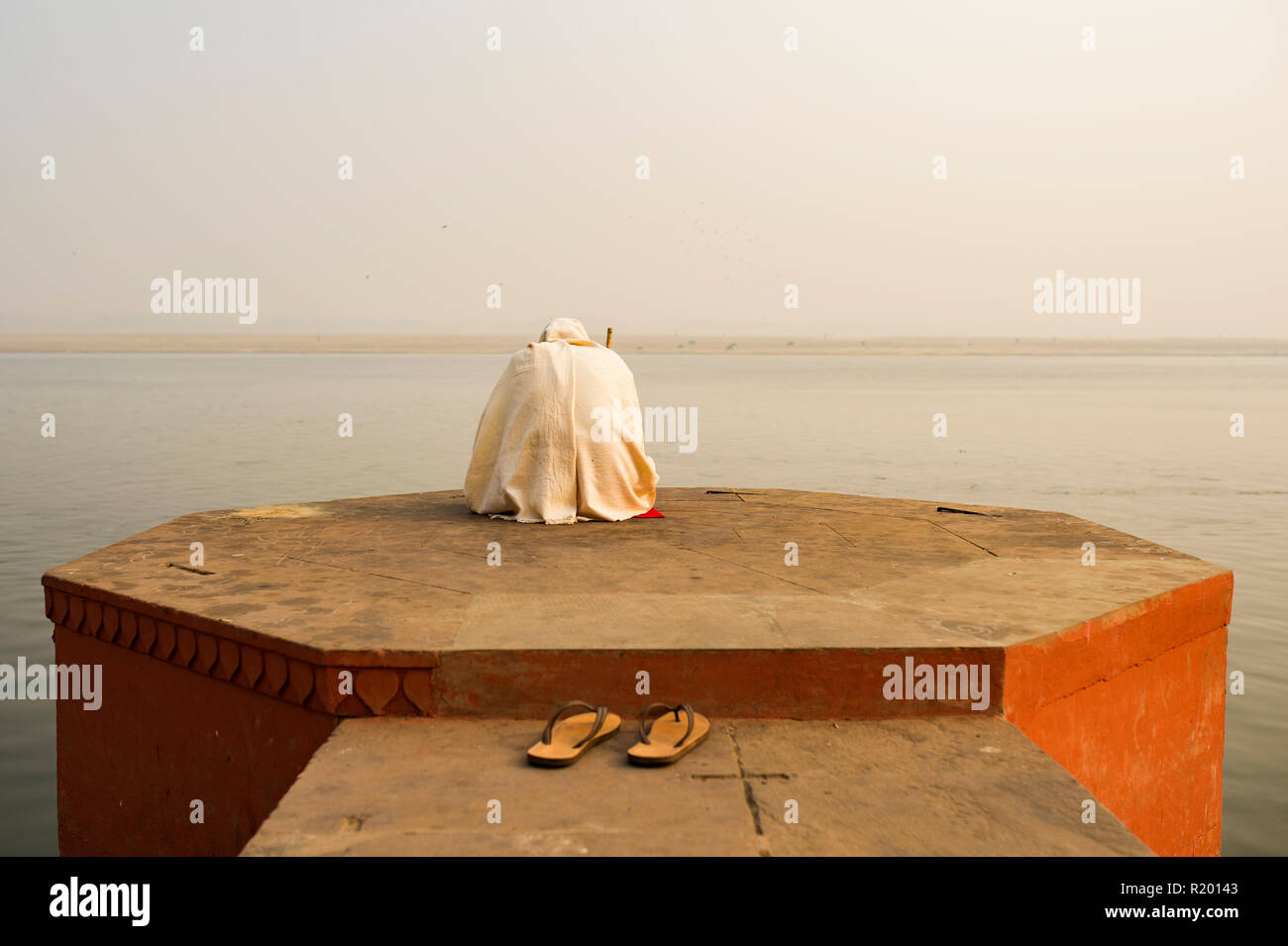 A holy man dressed in white is praying and meditating on one of the many Ghats of Varanasi in front of the sacred river Ganges, India. Stock Photo
