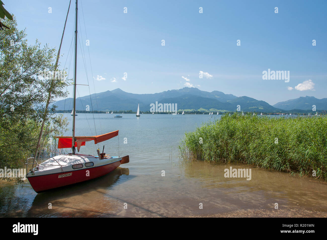 Lake Chiemsee. Sailboat at the shore with island Herreninsel in background, Bavaria, Germany - Stock Image