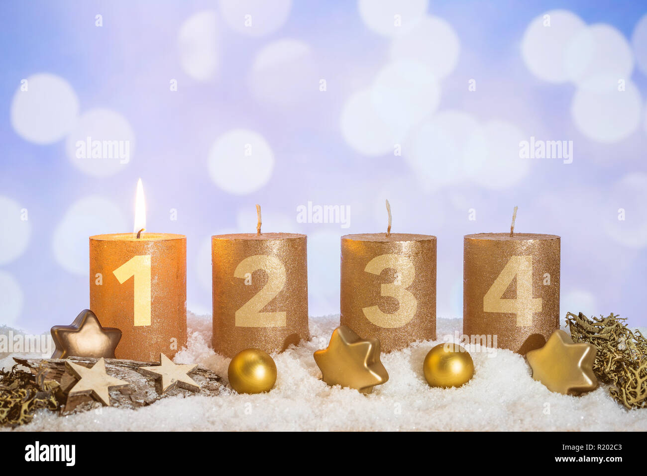 Four numbered gold advent candles with first candle lit and christmas decoration lying in snow as template - Stock Image