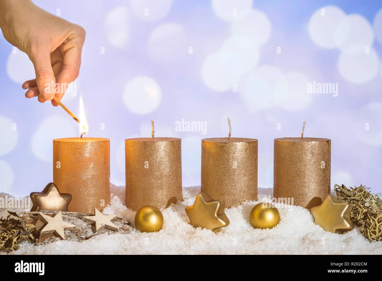 Four gold advent candles with first candle lit by hand with match and christmas decoration lying in snow as template - Stock Image