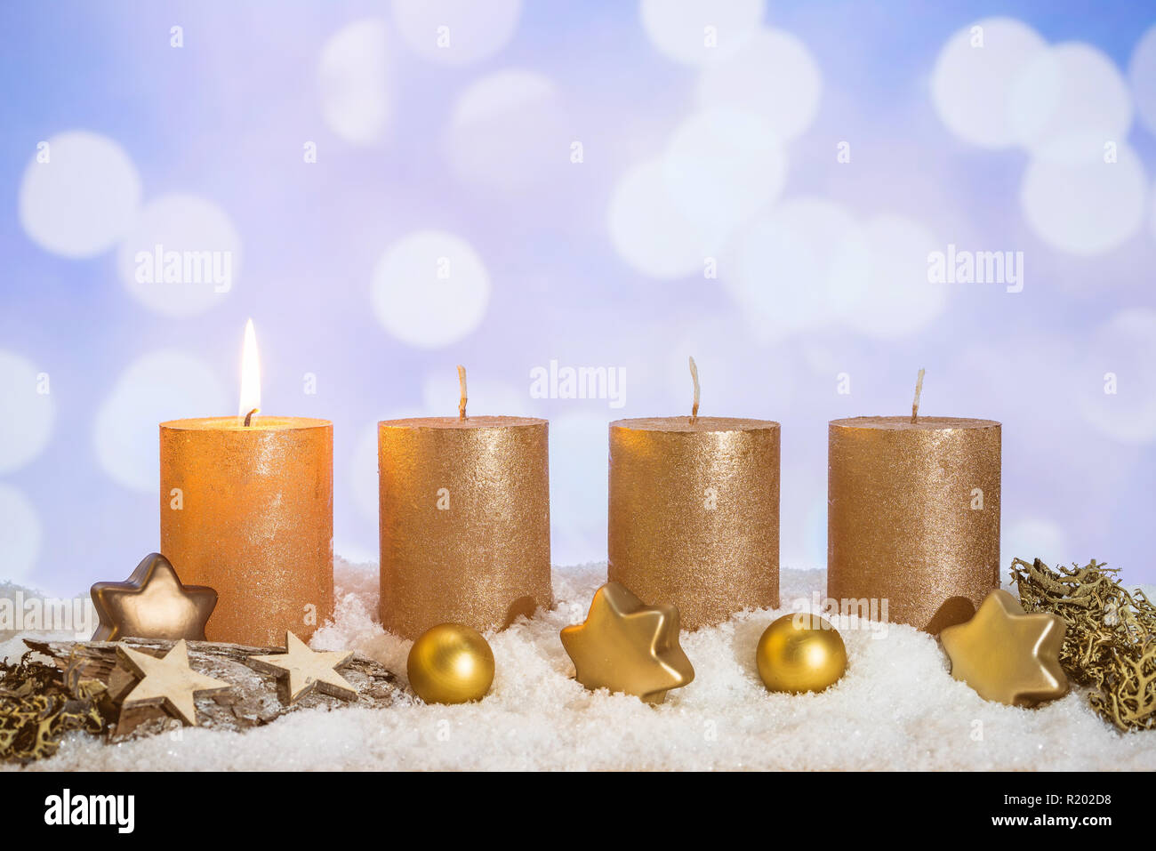 Four golden advent candles with first candle lit and christmas decoration lying in snow as template - Stock Image