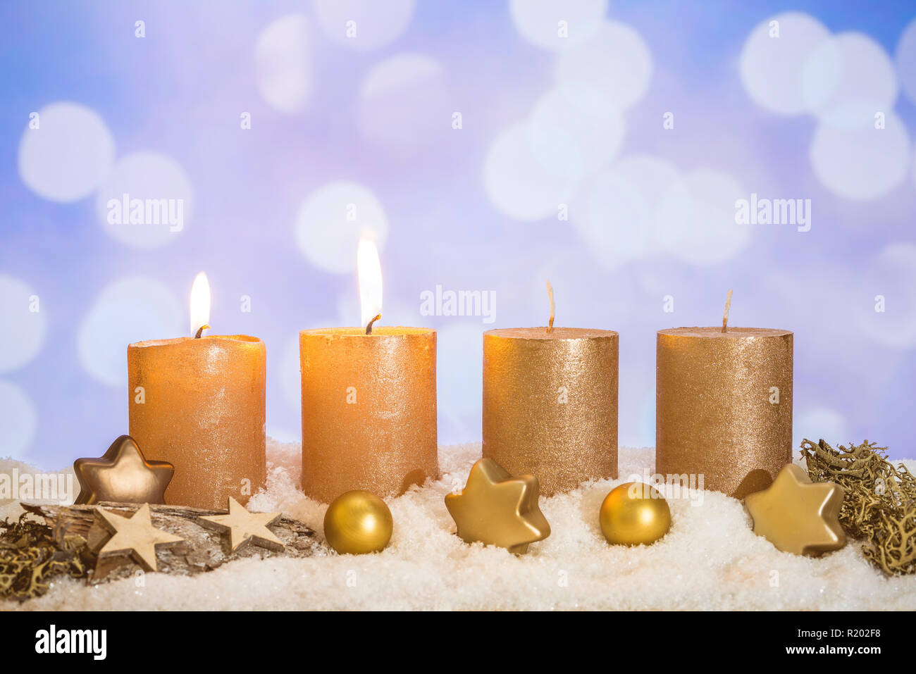 Four golden advent candles with two candles lit and christmas decoration lying in snow as template - Stock Image