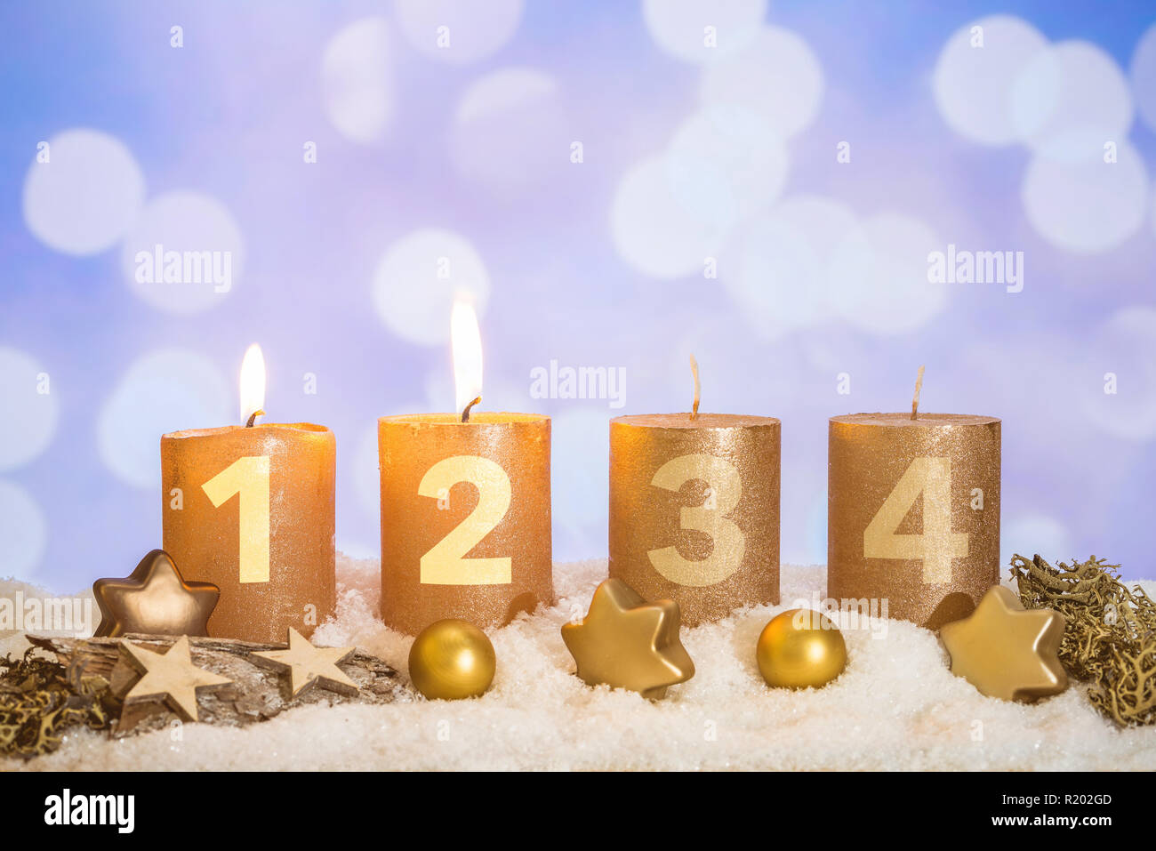 four numbered gold advent candles with two candles lit and christmas