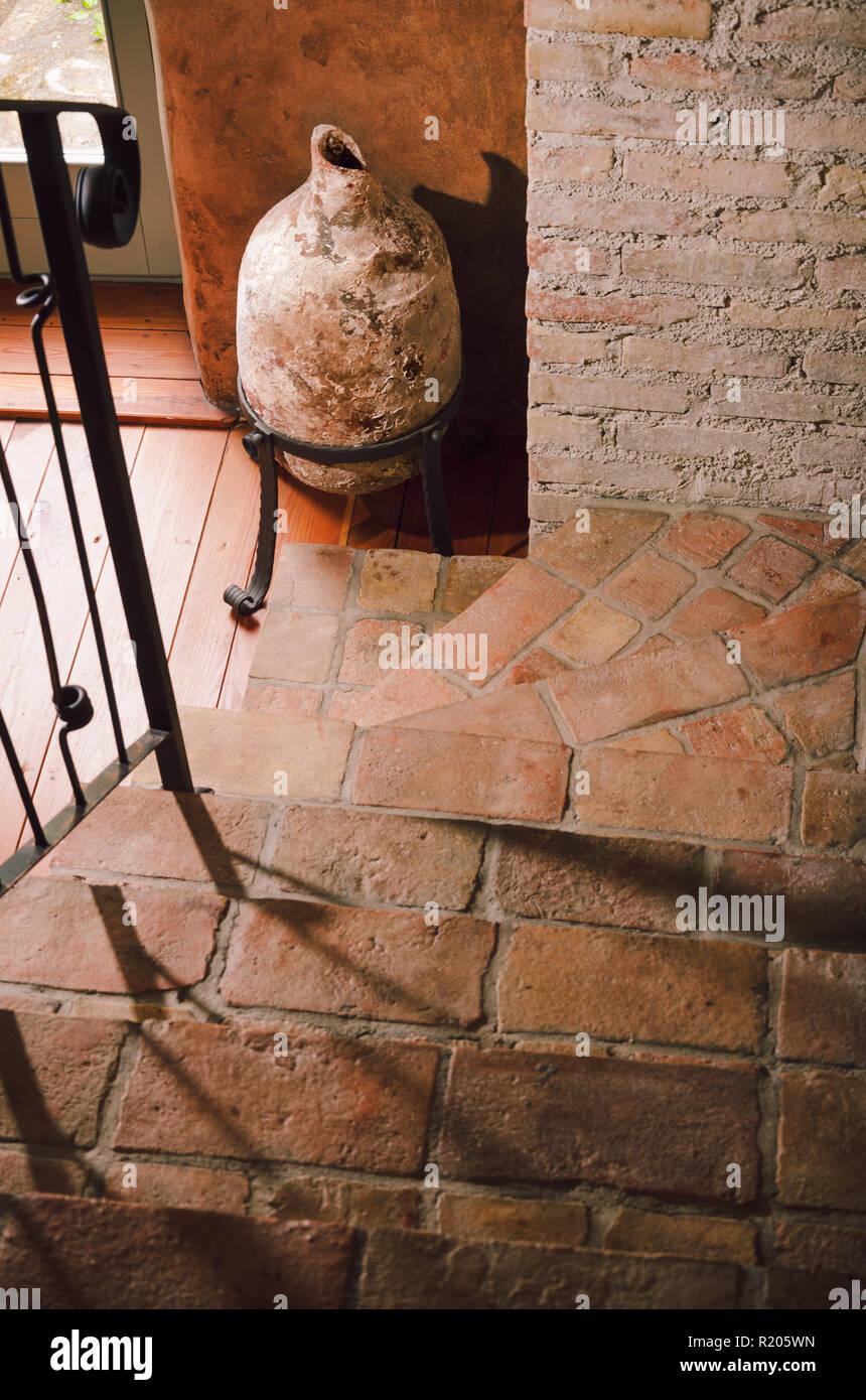Big ancient roman amphora, jug and old stairways, indoor interior decoration - Stock Image