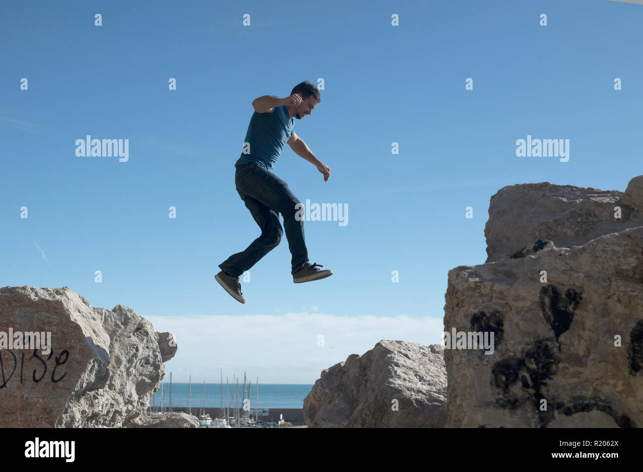 Young man leaping across rocks in Garaff Spain - Stock Image