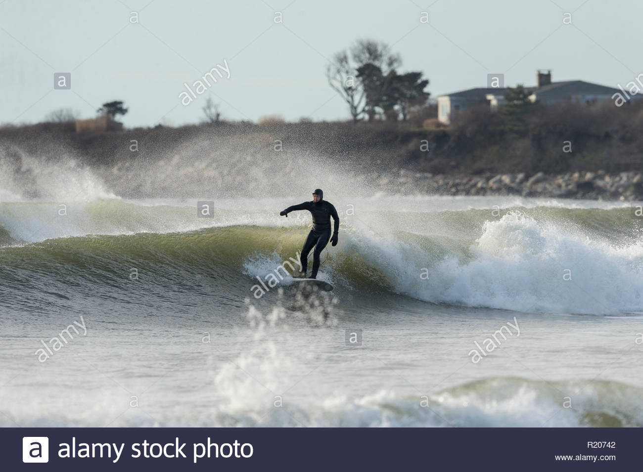 Little Compton, Rhode Island, USA - January 17, 2016: Surfer on middle wave in a set at Goosewing Beach - Stock Image