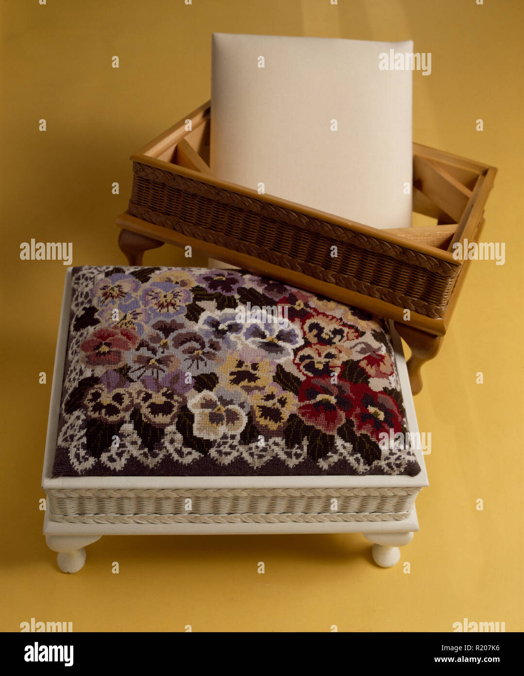 Close-up of a pansy themed cross stitch footstool - Stock Image