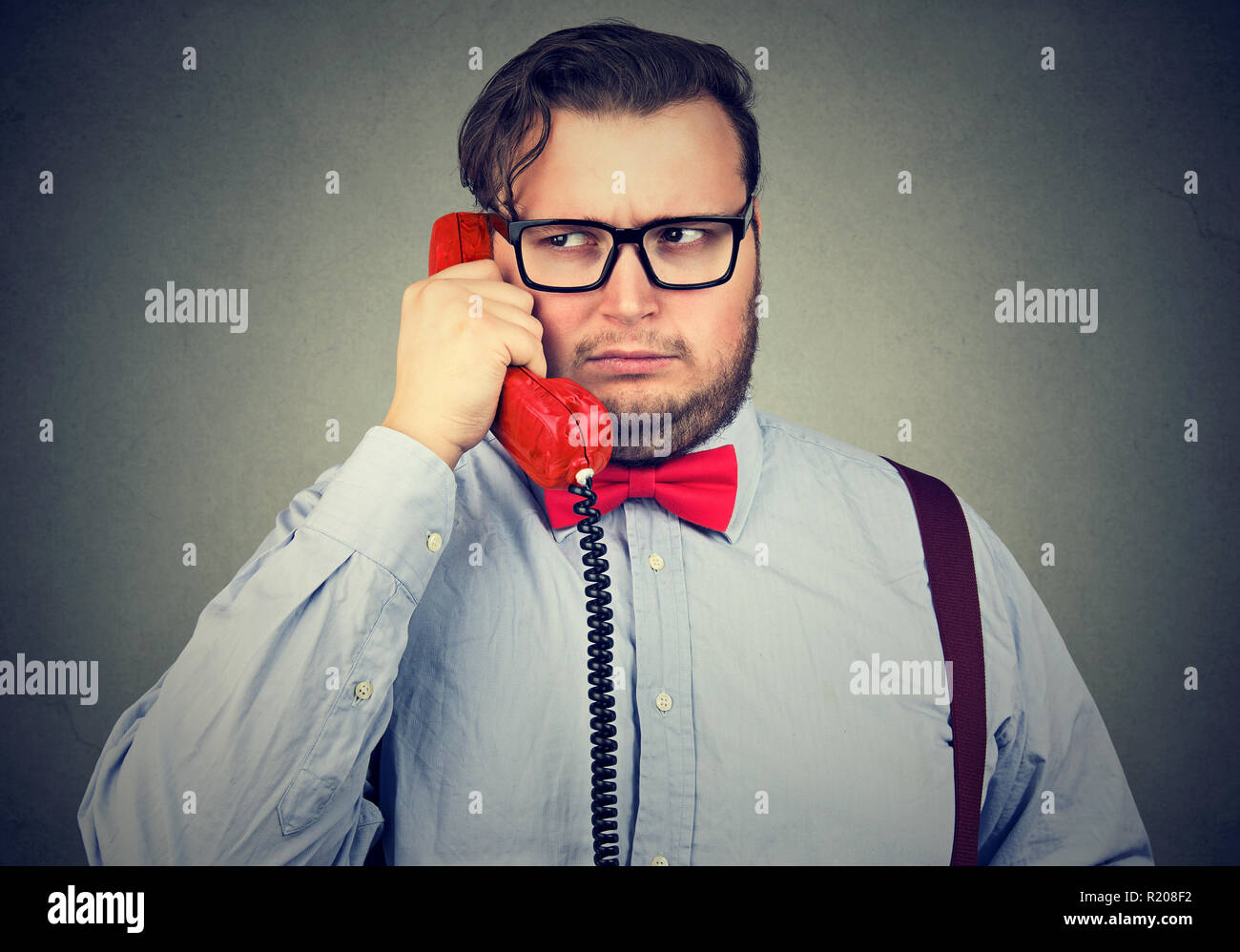 Young frowning man having problem while speaking on red telephone feeling confused and suspicious on gray background - Stock Image
