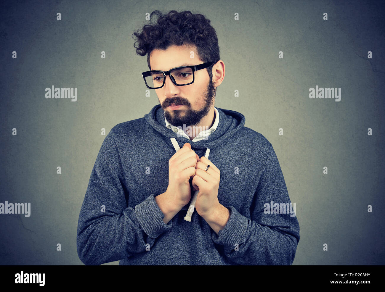 Young bearded man pointing feeling shy and guilty in awkward situation - Stock Image