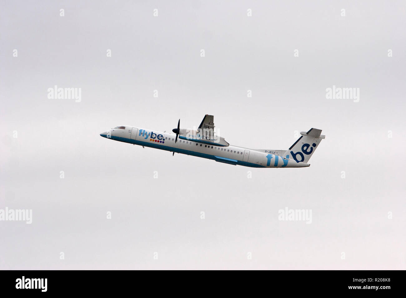 Flybe Dash 8-400 climbing out from Manchester Airport - Stock Image
