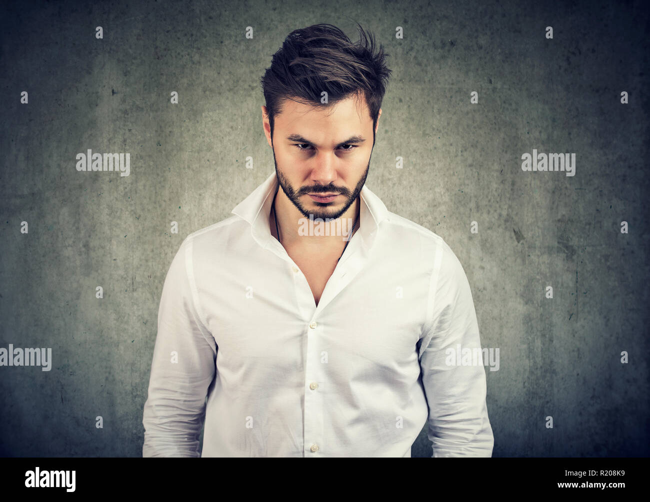Adult bearded man in white shirt looking with anger and offense at camera on gray background - Stock Image