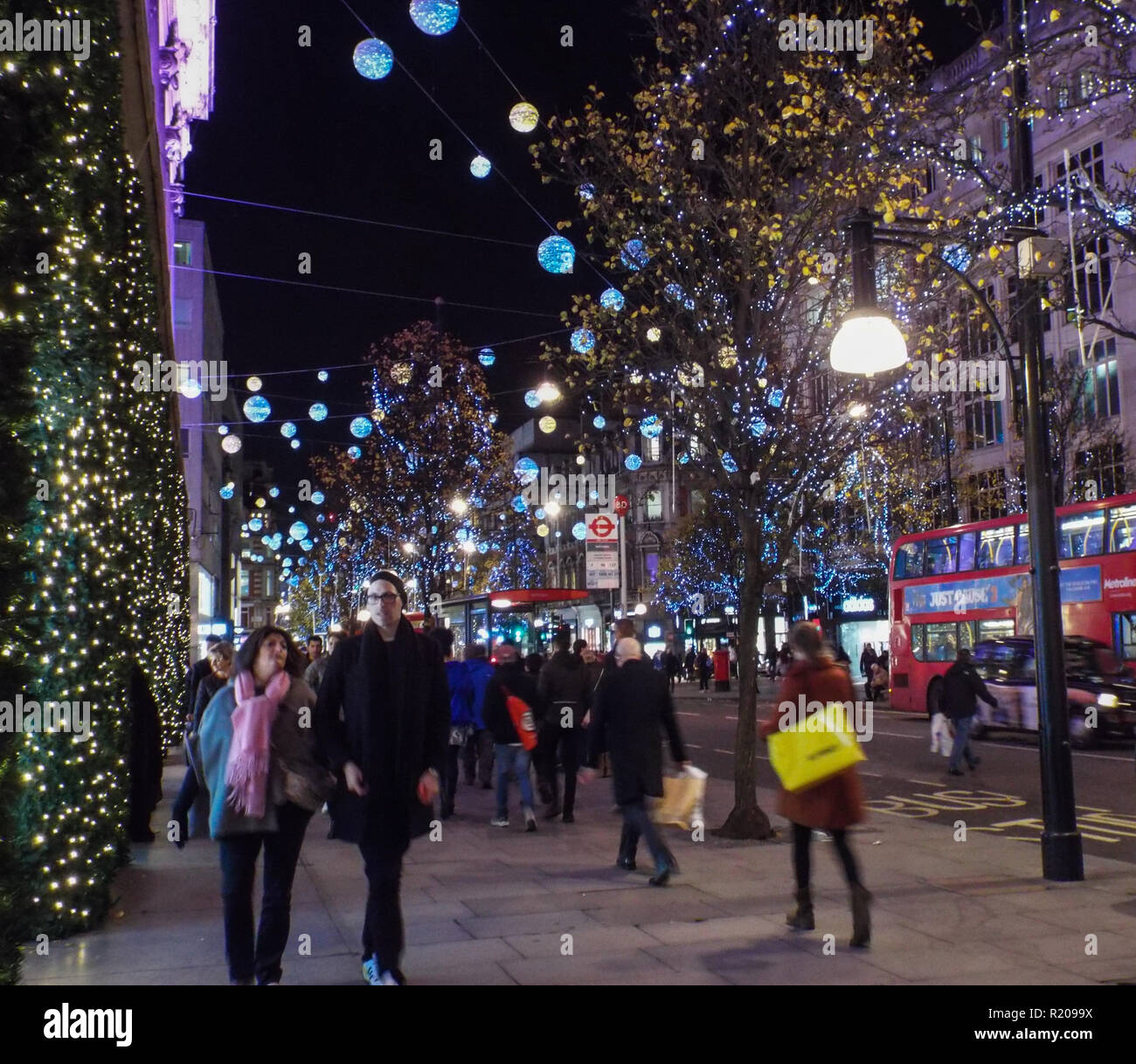 Christmas Lights and shoppers on Oxford St. Central London, England.  night time, horizontal. Dec.2015 - Stock Image
