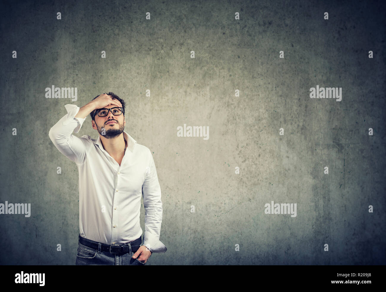 Young casual man in white shirt and glasses having problems and looking up in challenge on gray wall background - Stock Image
