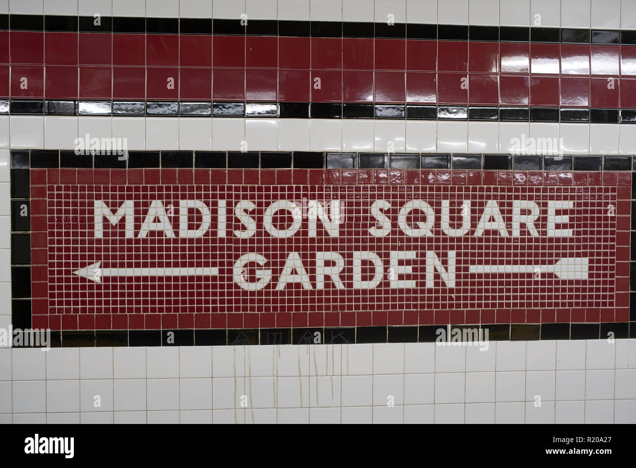 Madison Square Garden mosaic direction sign inside subway station in New York City. - Stock Image