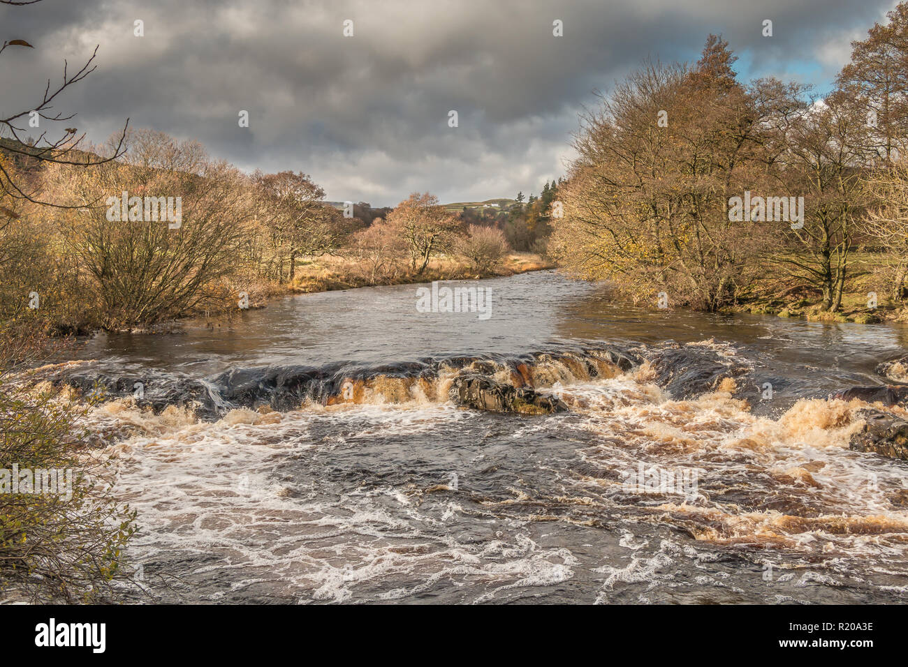 North Pennines AONB Landscape, cascade on the river Tees from the Pennine Way between Low and High Force Waterfalls in autumn sunshine and a dark sky Stock Photo