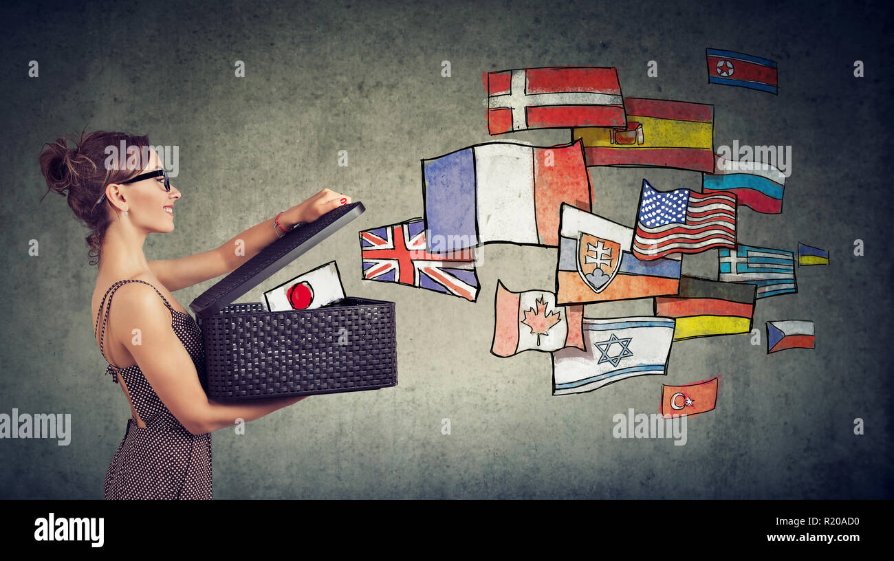 Young woman speaks different languages opening a box with international flags flying away - Stock Image