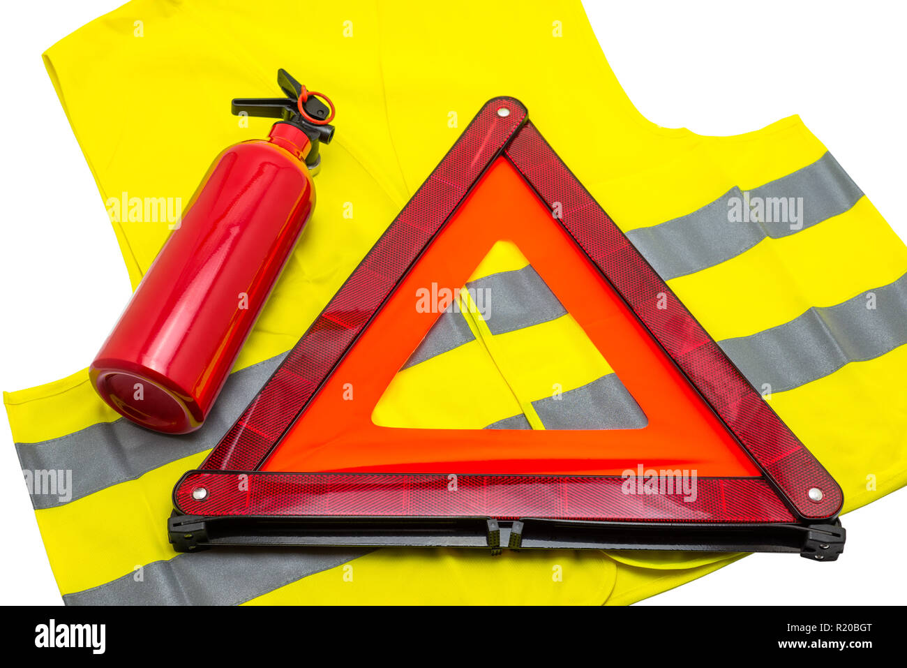 The fire extinguisher and reflective warning triangle lie on the reflective vest, isolated on a white background with a clipping path. - Stock Image