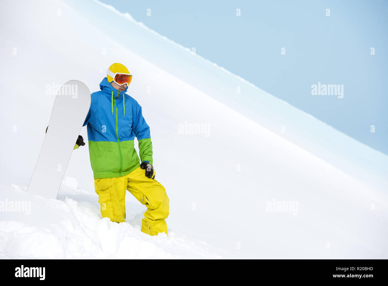 Snowboarder stands on backcountry slope and holds snowboard. Ski concept - Stock Image