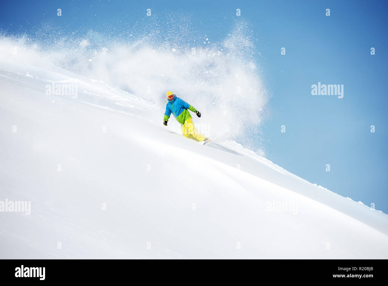 Fast snowboarder at offpiste slope with powder snow tail. Freeride ski concept - Stock Image