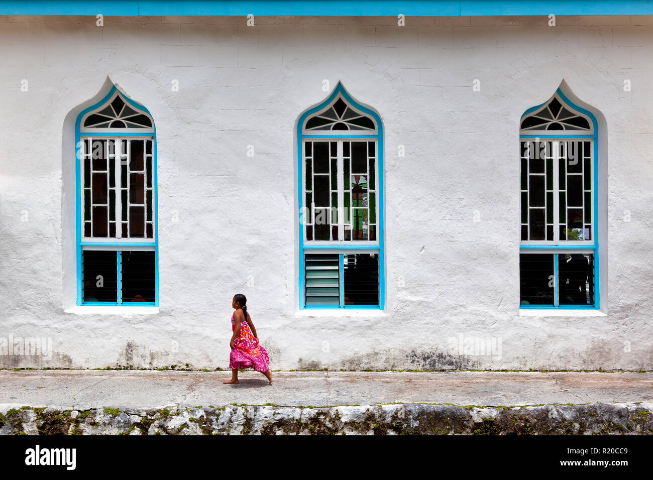 Local Cook Islander girl skipping out of Sunday Mass, Rarotonga, Cook Islands. - Stock Image