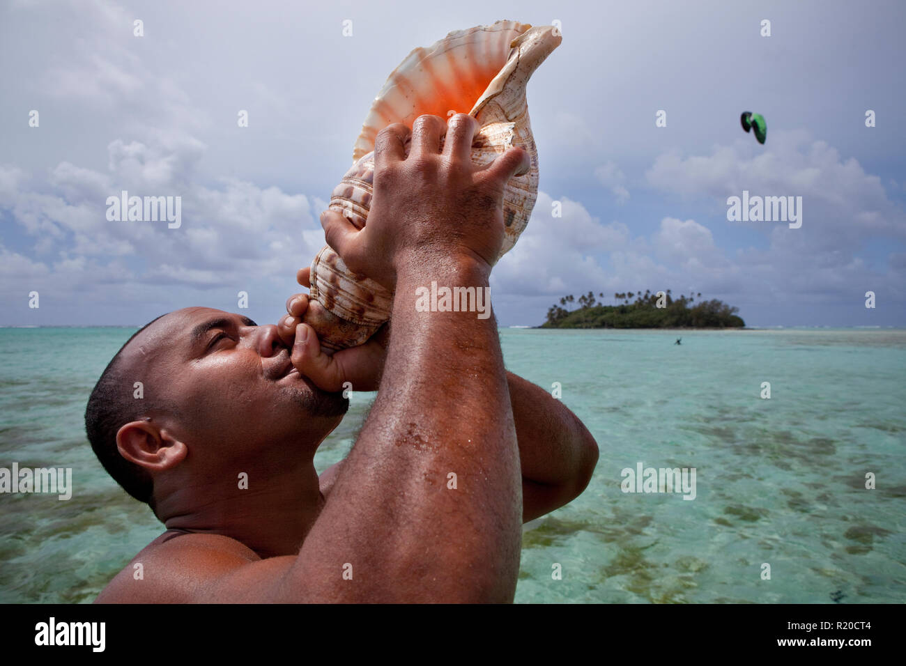 Local guide sounding off on a conch horn in Muri Lagoon, Rarotonga, Cook Islands. - Stock Image
