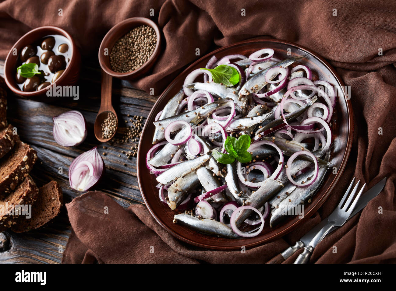 salted sprats salad with red onion rings on a earthenware plate on a old rustic wooden table with olives in bowl and rye sliced bread on an old rustic - Stock Image