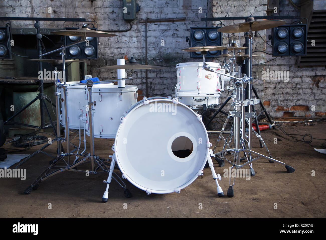 White drum Set in industrial room on white brick background. - Stock Image
