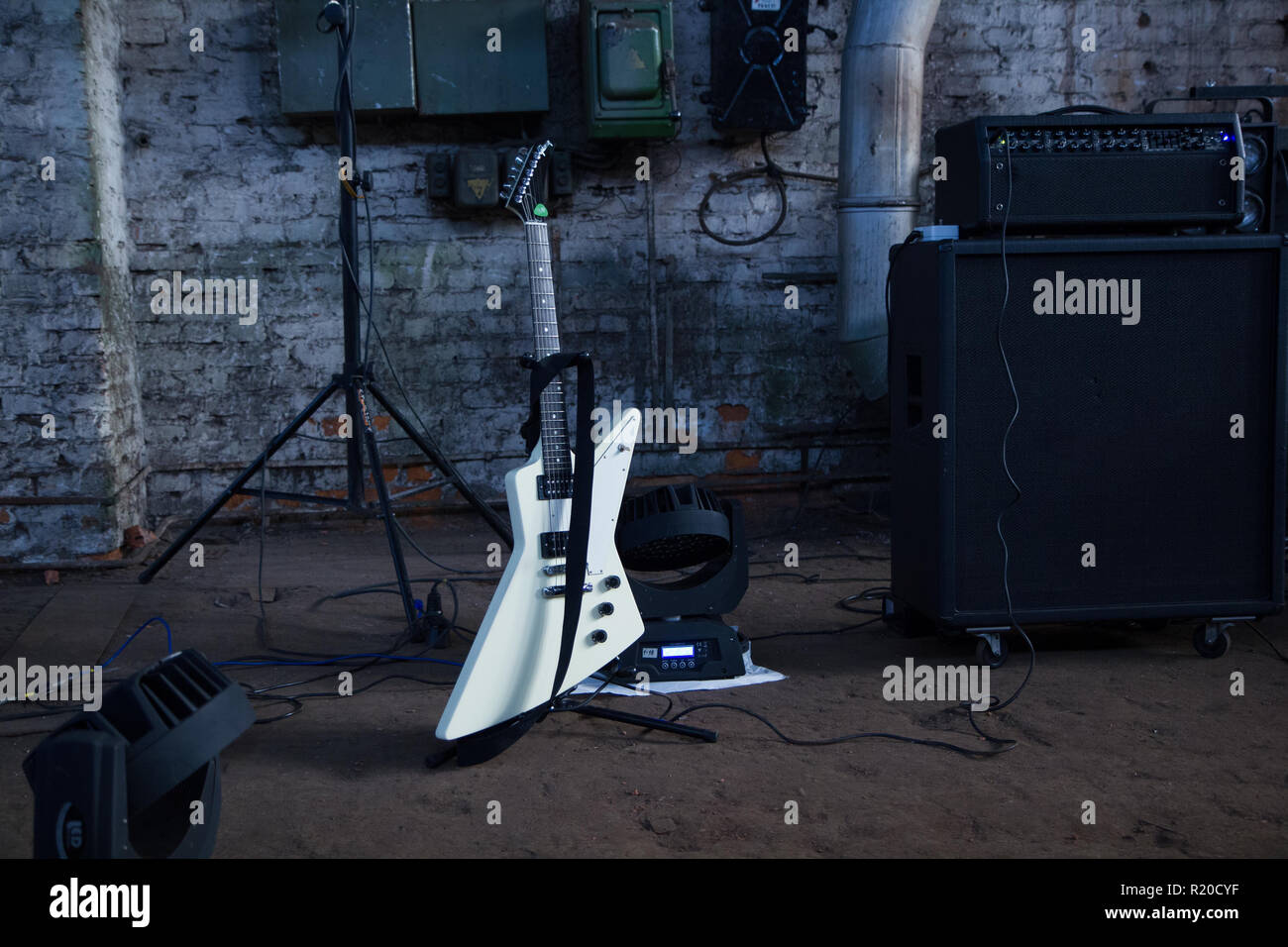 White electric guitar and amplifier on a industrial background. - Stock Image