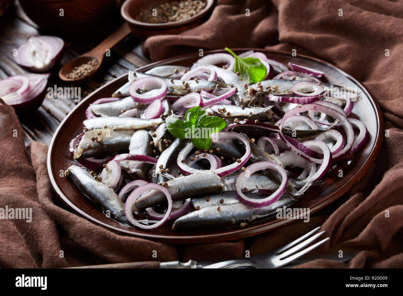 salted sprats marinated with red onion rings on an earthenware plate  coriander seeds, brown cloth, fork and knife on an old rustic wooden table, view - Stock Image