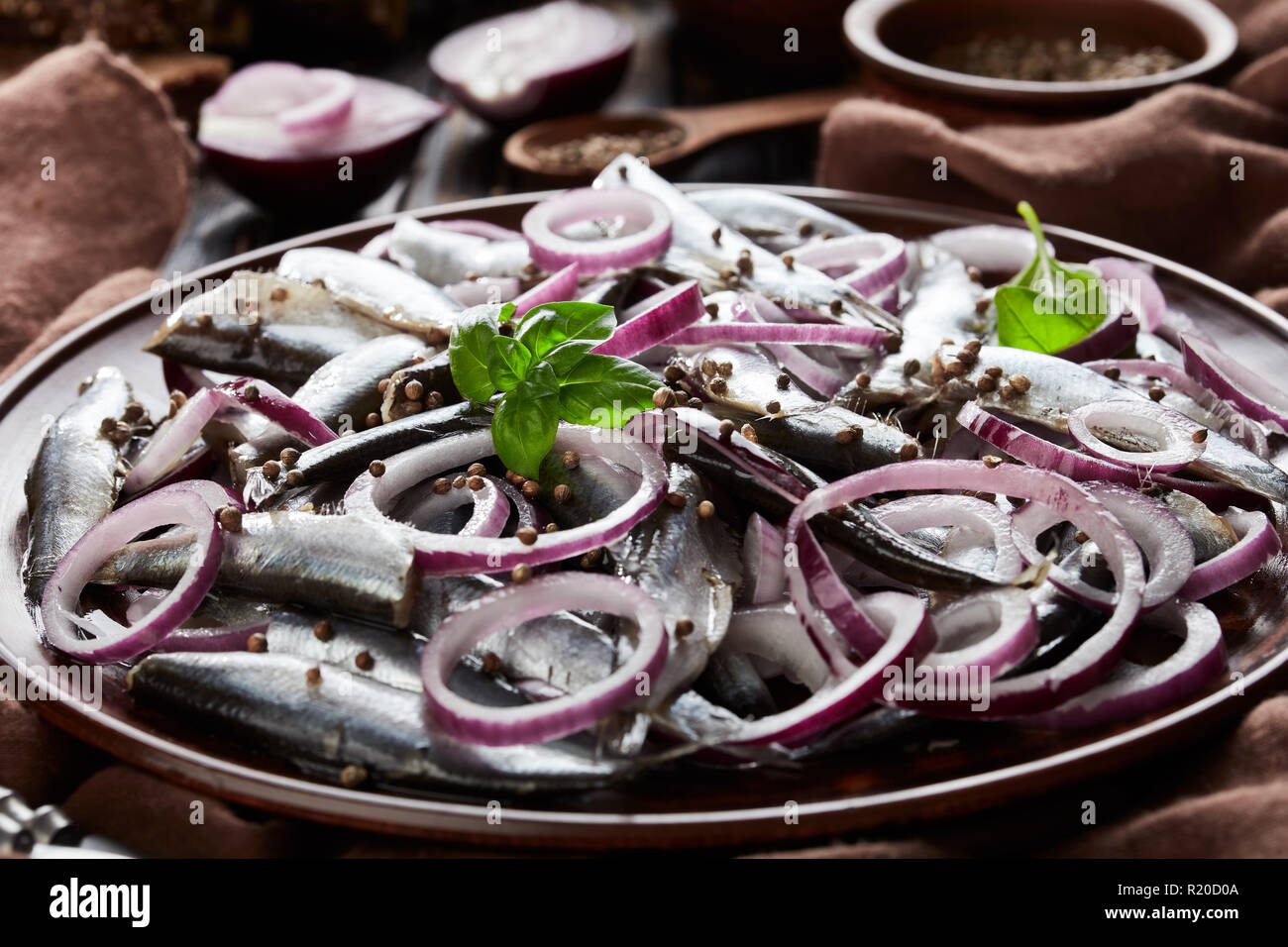 cloth-up of salted sprats marinated with red onion rings on an earthenware plate  coriander seeds, brown cloth, fork and knife on an old rustic wooden - Stock Image