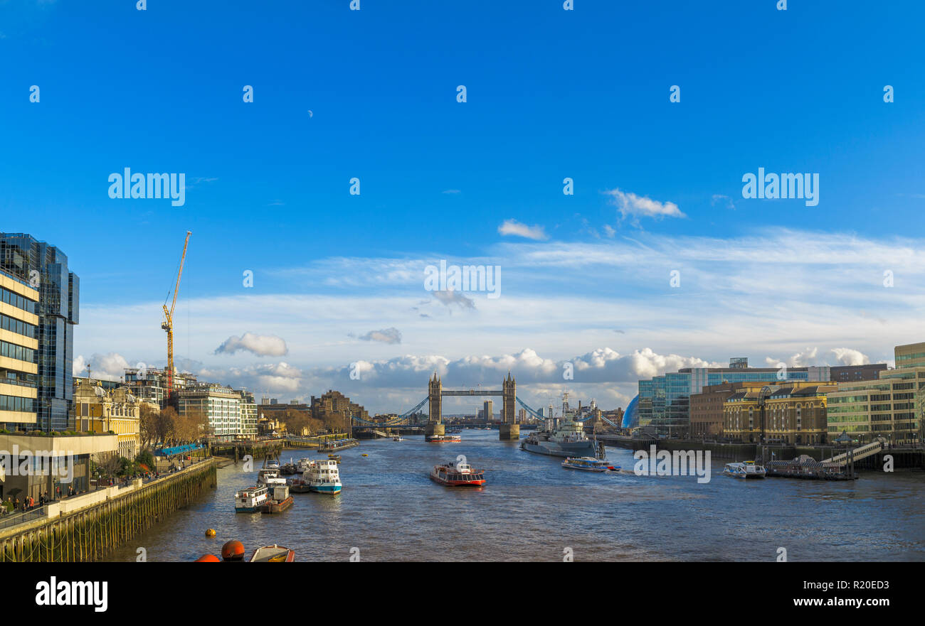 View from London Bridge of the River Thames and the Pool of London to Tower Bridge and HMS Belfast moored by Hays Galleria on a sunny day in winter - Stock Image