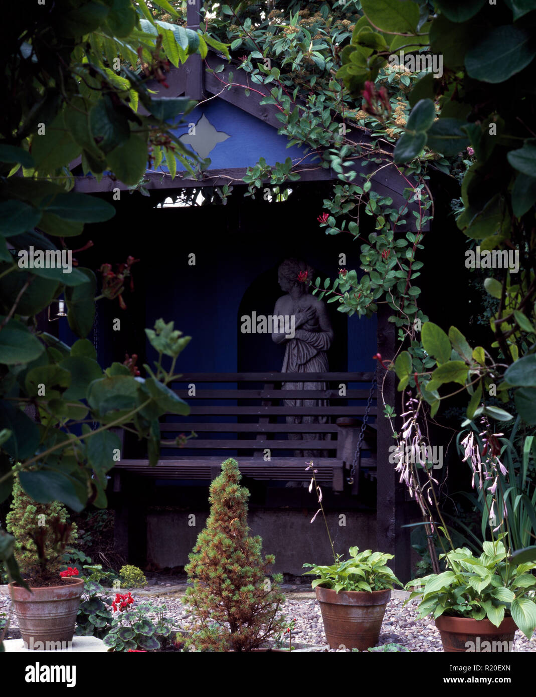 Green climbing plants around blue painted arbour with statue - Stock Image