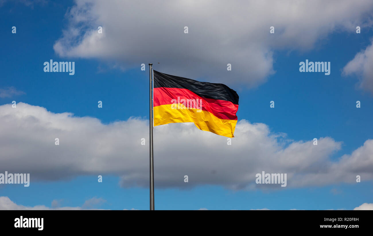 German flag waving on a flagpole against blue sky with clouds, wallpaper. - Stock Image