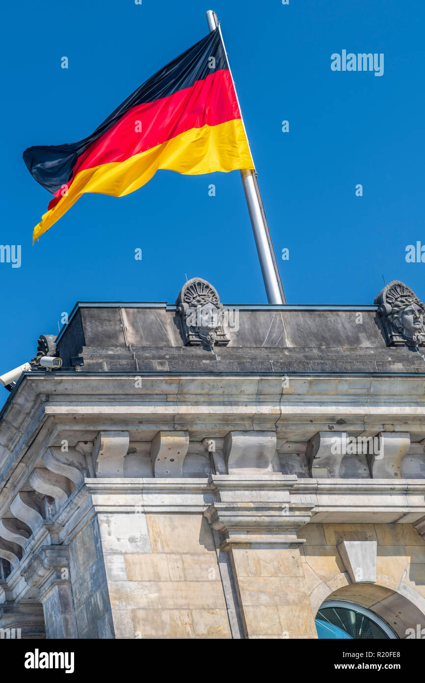 The German National Flag flies above the Reichstag in Berlin, Germany. - Stock Image