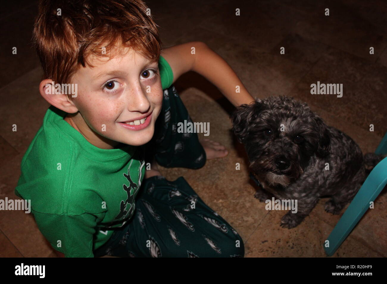 Close up of red headed boy with freckles rubbing his small black dog - Stock Image