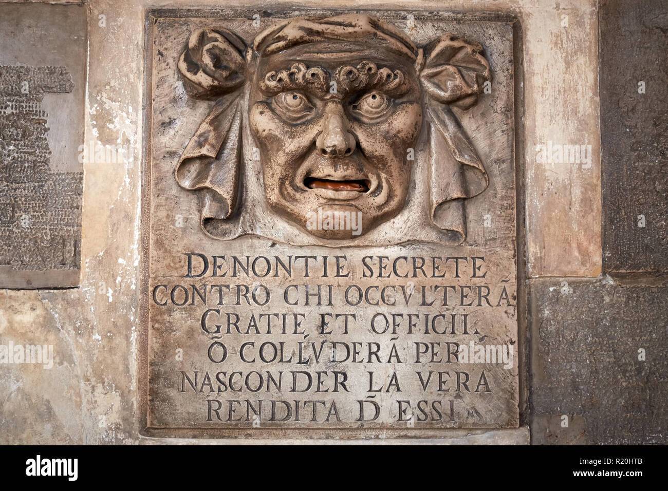 A carving above a letter box inside the Doge's palace, Venice with the text Secret denunciations against anyone who will conceal favors and services Stock Photo