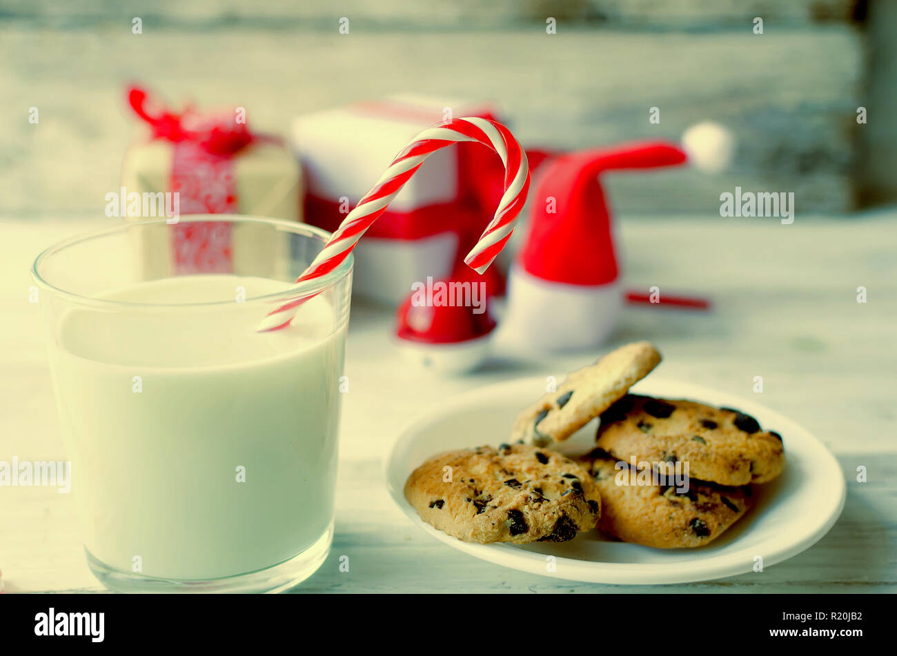 A glass of milk with candy and cookies with chocolate chip  for Santa on christmas eve on white wooden table. Christmas lcard. toned photo Stock Photo