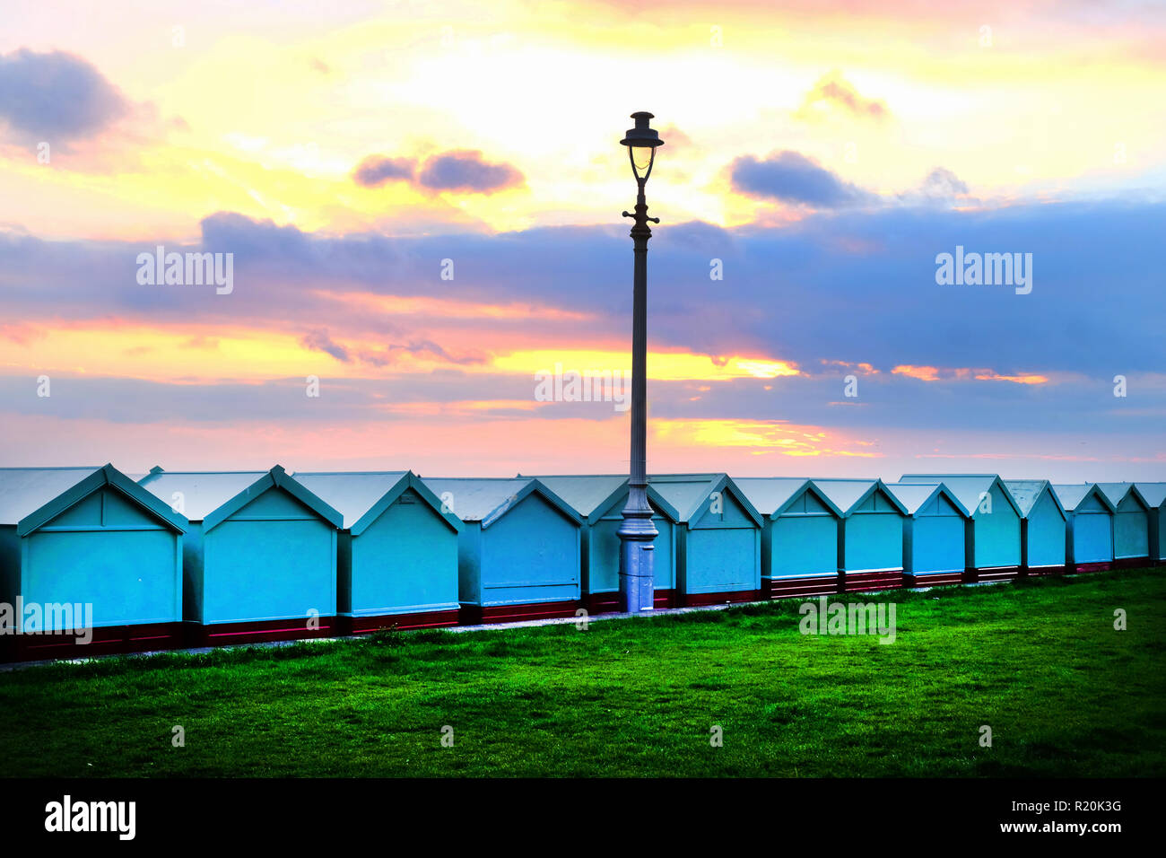 Brighton seafront a line thirteen beach huts, with a victorian street lamp in the middle the sun is setting and the sky is glowing yellow, red, and or Stock Photo