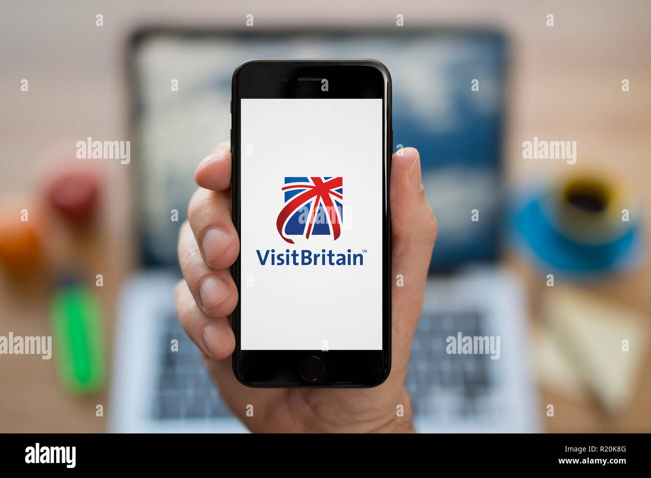 A man looks at his iPhone which displays the Visit Britain logo, while sat at his computer desk (Editorial use only). - Stock Image
