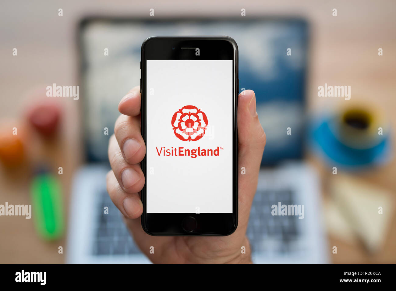 A man looks at his iPhone which displays the Visit England logo, while sat at his computer desk (Editorial use only). - Stock Image