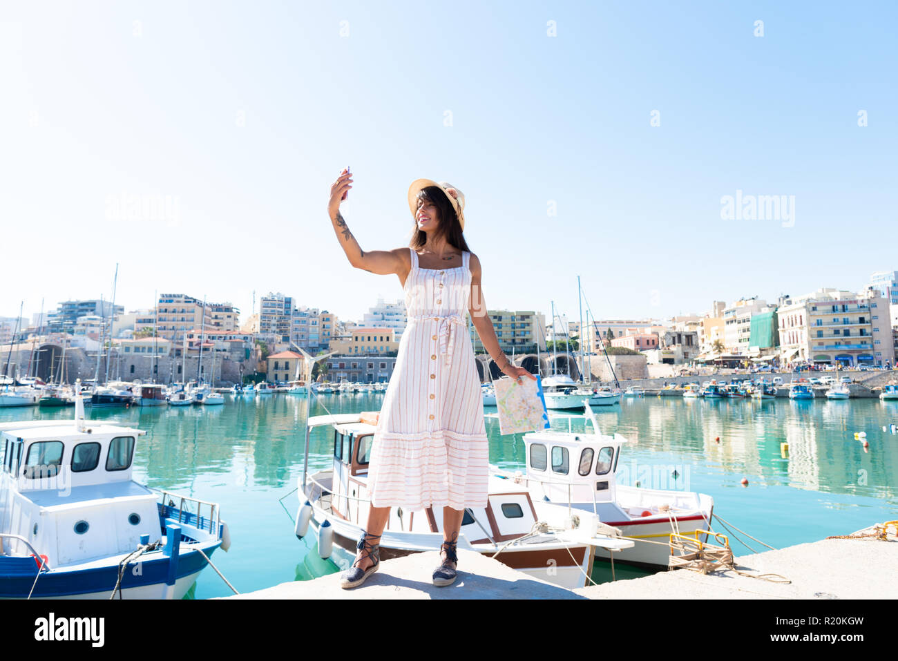 Traveling tourist woman on vacation in Heraklion Crete taking selfies at the port. Lovely elegant girl takes selfies visiting the famous Mediterranean - Stock Image