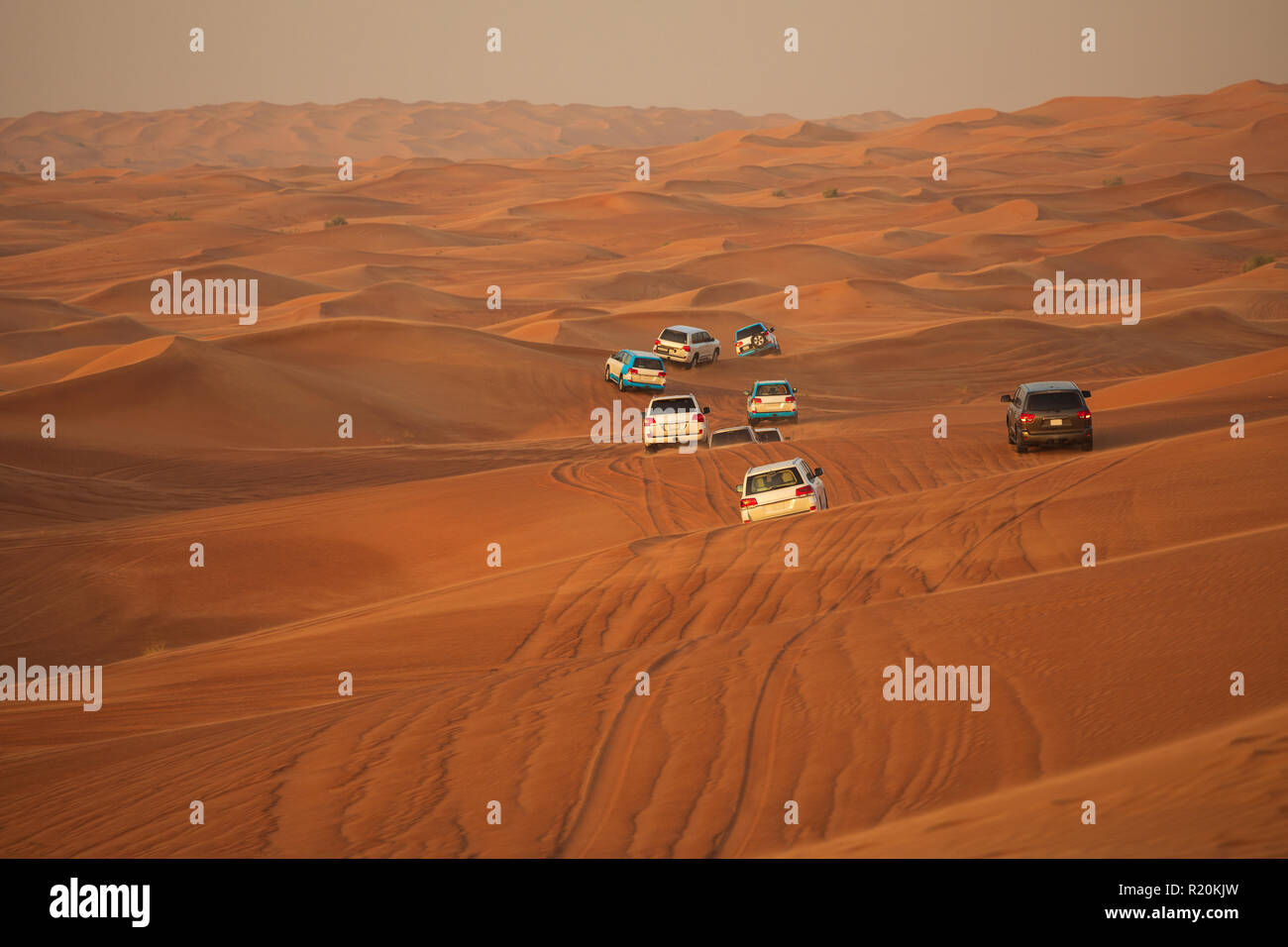 Off-road adventure with SUV driving in Arabian Desert at sunset. Offroad vehicle bashing through sand dunes in Dubai desert. Traditional entertainment - Stock Image