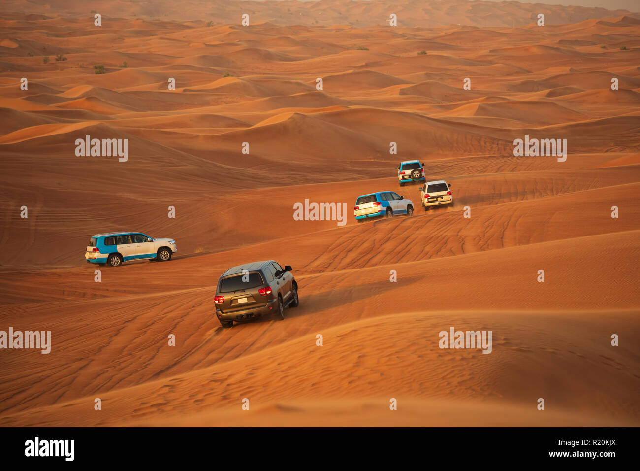 Off-road adventure with SUVs driving in Arabian Desert at sunset. Traditional entertainment for tourists with vehicle bashing through sand dunes in Du - Stock Image