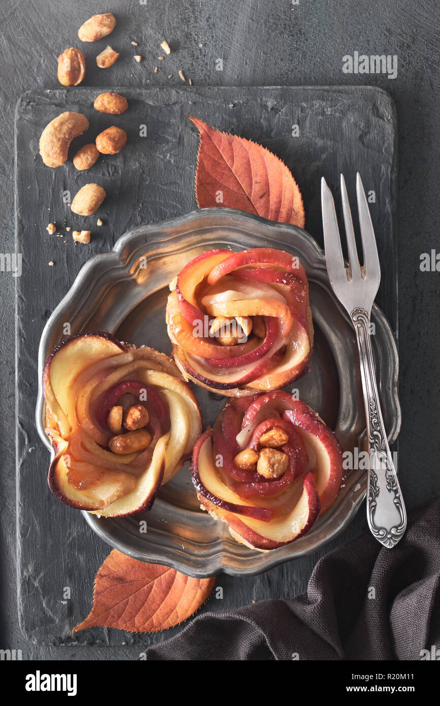 Three homemade puff pastries with rose shaped apple slices on metal plate. Top lay on wooden board with Autumn leaves and caramelized nuts. Stock Photo