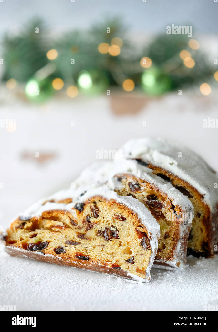 Christmas stollen on white festive background with fir twigs and trinkets. Traditional German dessert for Christmas celebration. - Stock Image