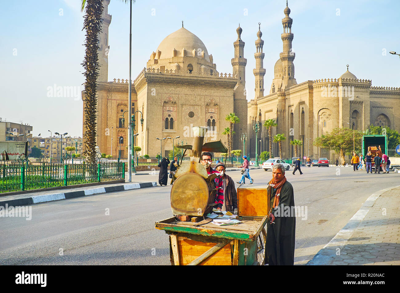 CAIRO, EGYPT - DECEMBER 21, 2017: Merchants push the food cart with oven on top, walking along Saladin Square, with a view on Sultan Hassan and the Ro - Stock Image