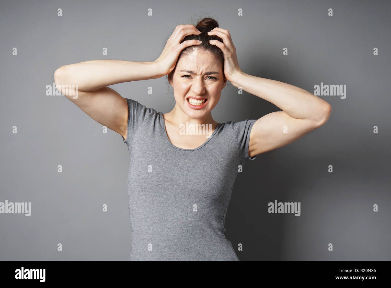 stressed young woman in despair or pain with hands holding head - gray background with copy space - Stock Image